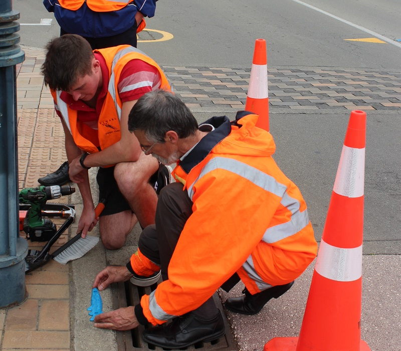 Picture of someone attaching a Blue Fish to a Timaru Storm Drain